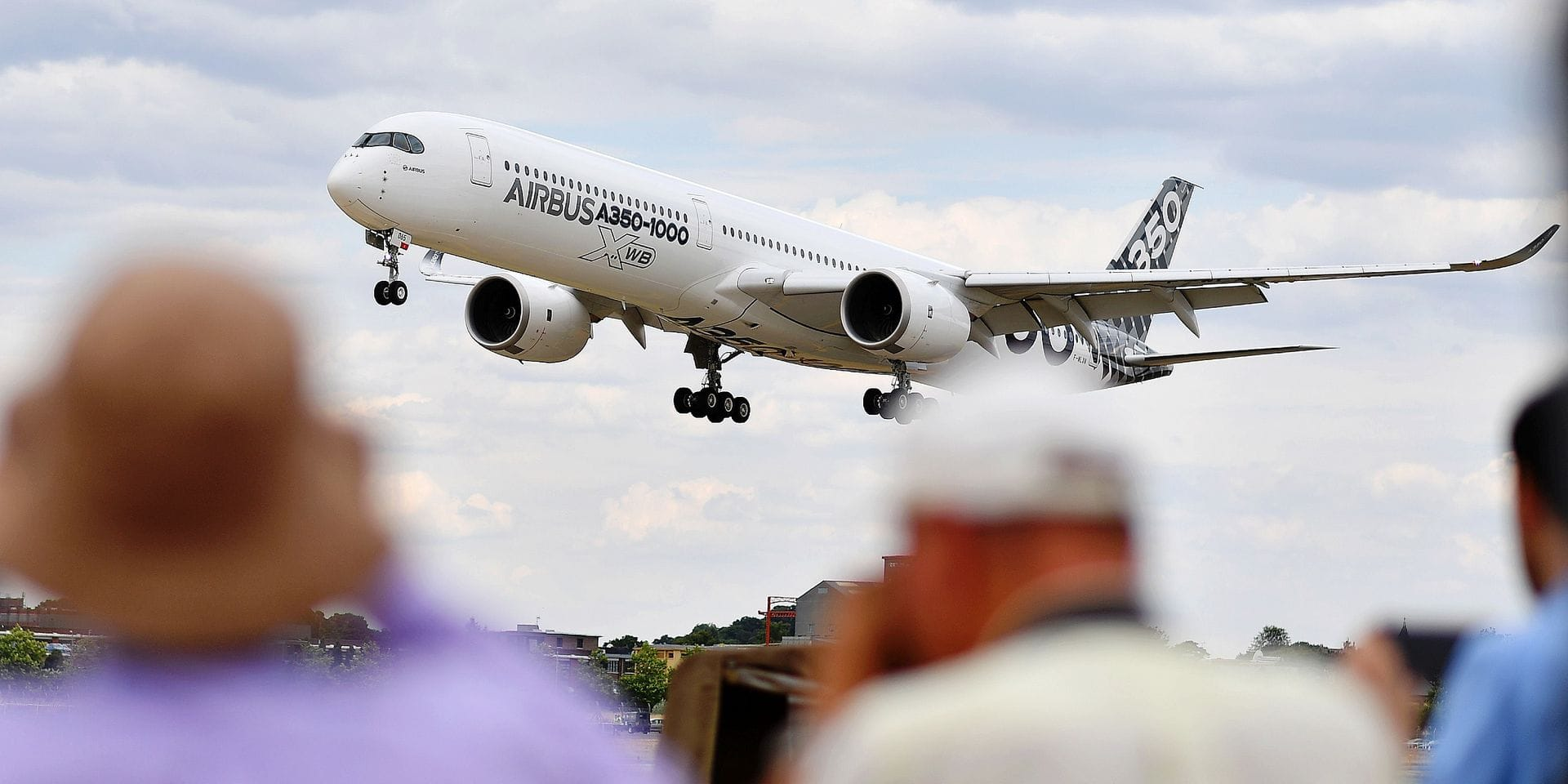 Visitors watch as an AirBus A330-900 Neo lands during the Farnborough Airshow, south west of London, on July 16, 2018. / AFP PHOTO / BEN STANSALL