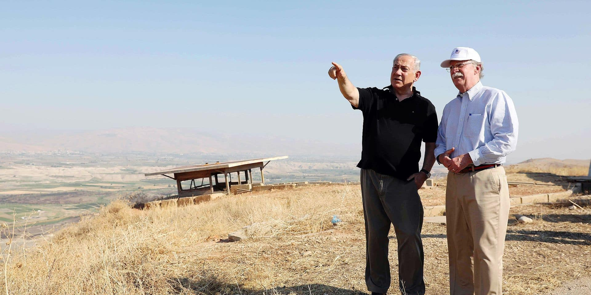 (FILES) In this file photo taken on June 23, 2019 Israeli Prime Minister Benjamin Netanyahu and then-US National Security Advisor John Bolton (R) visit an old army outpost overlooking the Jordan Valley between the Israeli city of Beit Shean and the West Bank city of Jericho, on June 23, 2019. - Israeli Prime Minister Benjamin Netanyahu issued a deeply controversial pledge on Tuesday to annex the Jordan Valley in the occupied West Bank if re-elected in September 17 polls. (Photo by ABIR SULTAN / POOL / AFP)