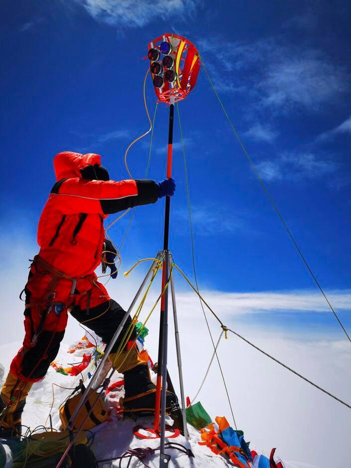 Un membre d'une équipe d'arpentage chinoise installe un équipement d'arpentage sur le sommet du mont Everest le 27 mai 2020.