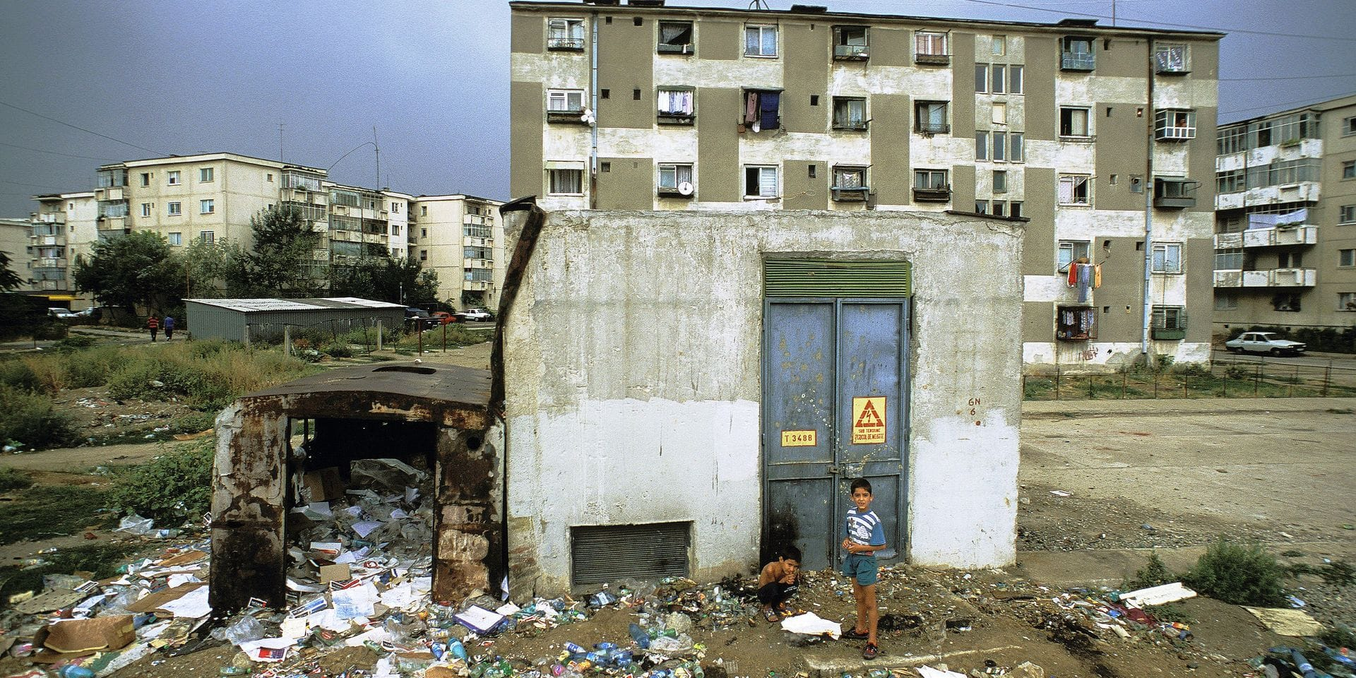 Romania, Bucarest, two gipsy kids seen from above near a garbage dump, garbages all around, buildings in the background