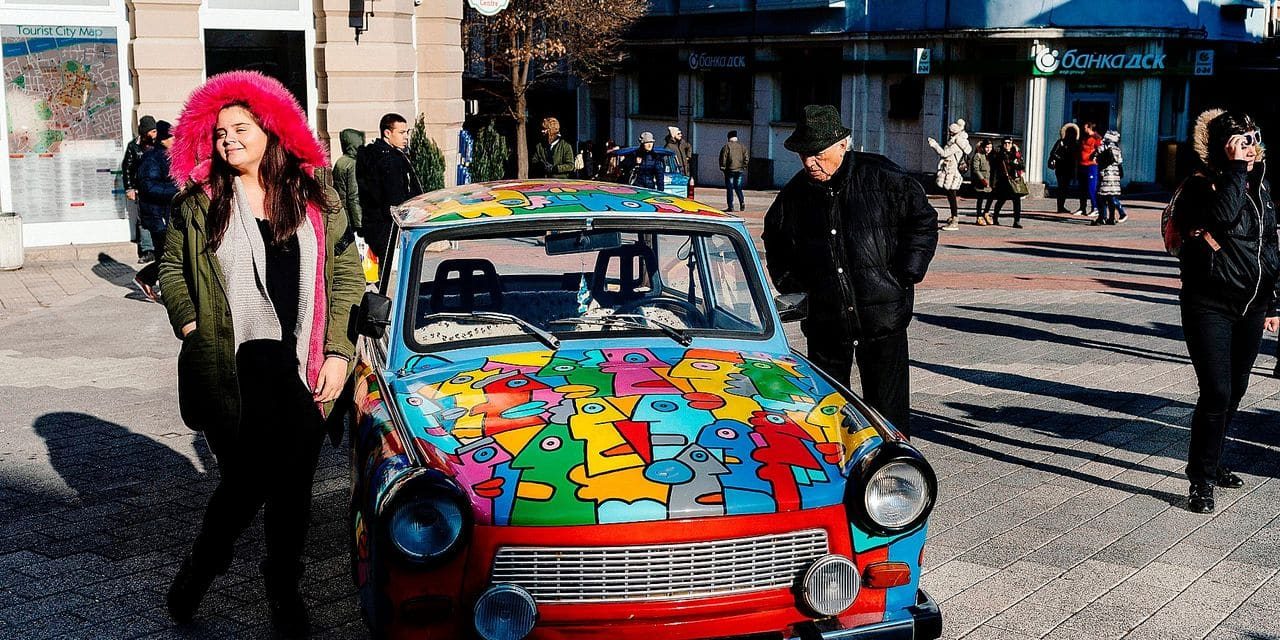 People look at a Trabant, a former East German car, painted by French artist Thierry Noir, as part of the exhibition 'Art Liberty - From the Berlin Wall to the Street Art', in the south-central Bulgarian town of Plovdiv on January 12, 2019. - Plovdiv and the southern Italian city of Matera have been selected as the 2019 European Capitals of Culture. (Photo by Dimitar DILKOFF / AFP) / RESTRICTED TO EDITORIAL USE - MANDATORY MENTION OF THE ARTIST UPON PUBLICATION - TO ILLUSTRATE THE EVENT AS SPECIFIED IN THE CAPTION