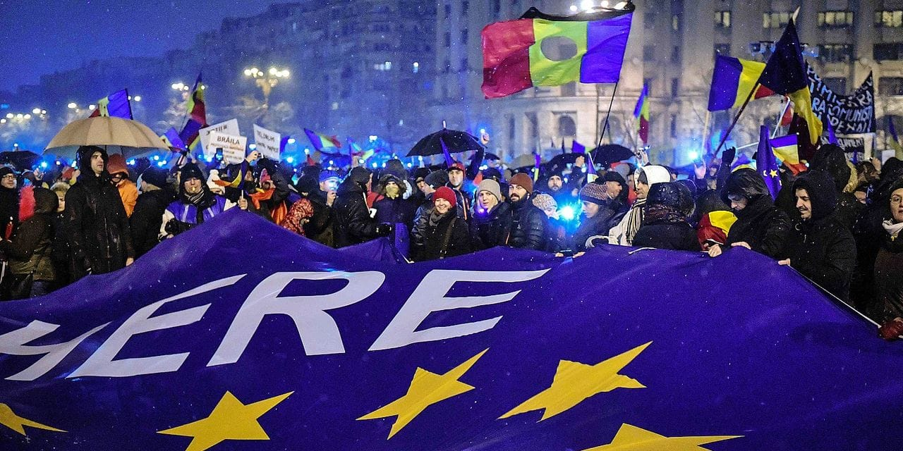 Demonstrators hold flags of Romania and of the European Union during an anti-government and anti-corruption protest in front of the Romanian Parliament building in Bucharest January 20, 2018. More than 30,000 people in Bucharest and in other cities across the country demonstrated against the policy of the ruling social democratic PSD party and a new legislation that has sparked concerns in Brussels and Washington about the shaky government's commitment to fighting endemic corruption. / AFP PHOTO / Daniel MIHAILESCU