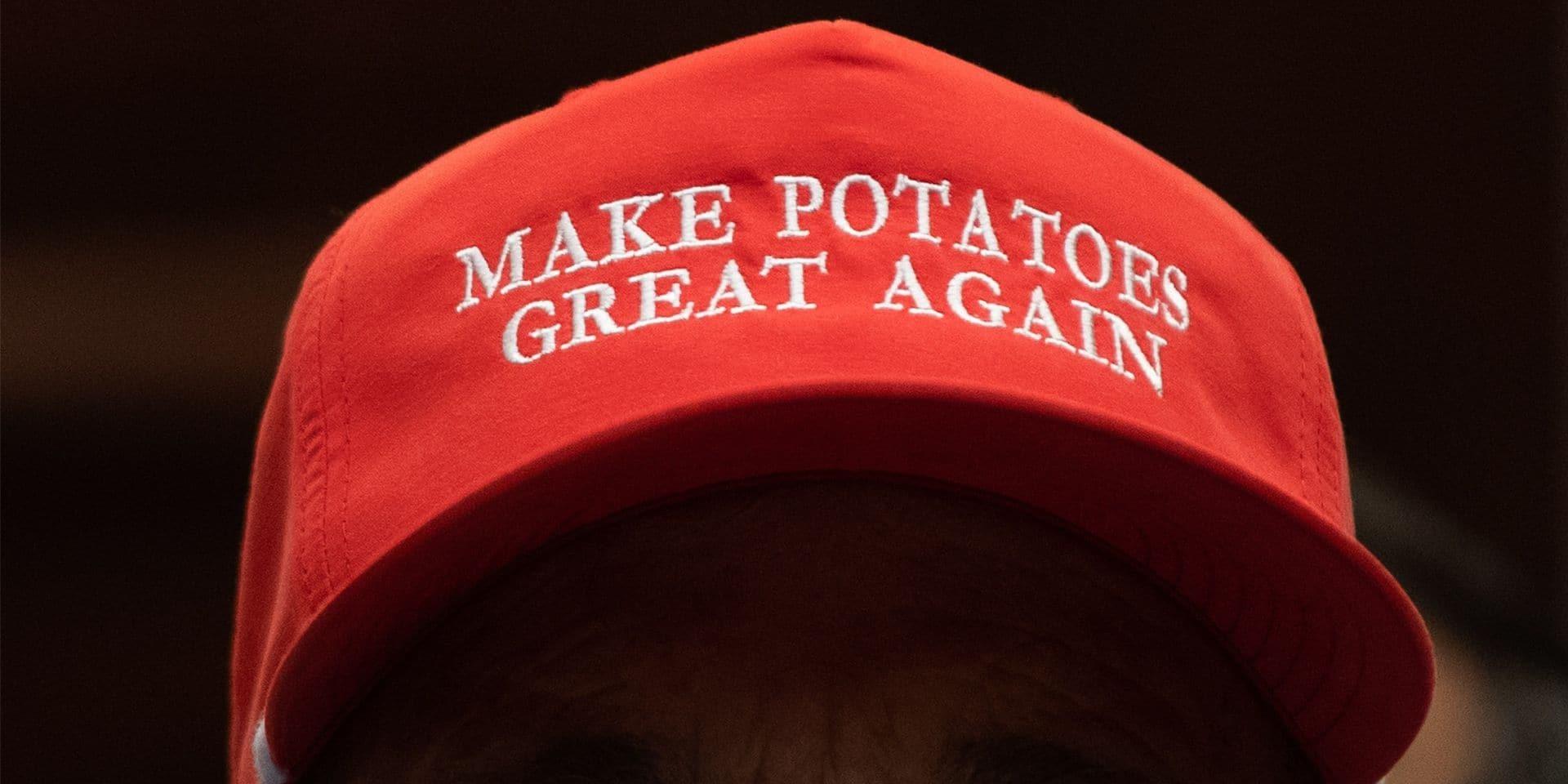 """Un fermier invité à la Maison blanche lors de la promulgation des subsides au secteur agricole porte une casquette parodiant le slogan de campagne de Trump """"Make America Great Again""""."""