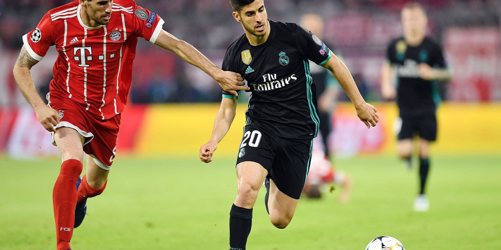 Real Madrid's Spanish midfielder Marco Asensio (R) challenges Bayern Munich's Spanish midfielder Javier Martinez during the UEFA Champions League semi-final first-leg football match FC Bayern Munich v Real Madrid CF in Munich in southern Germany on April 25, 2018. / AFP PHOTO / Christof STACHE