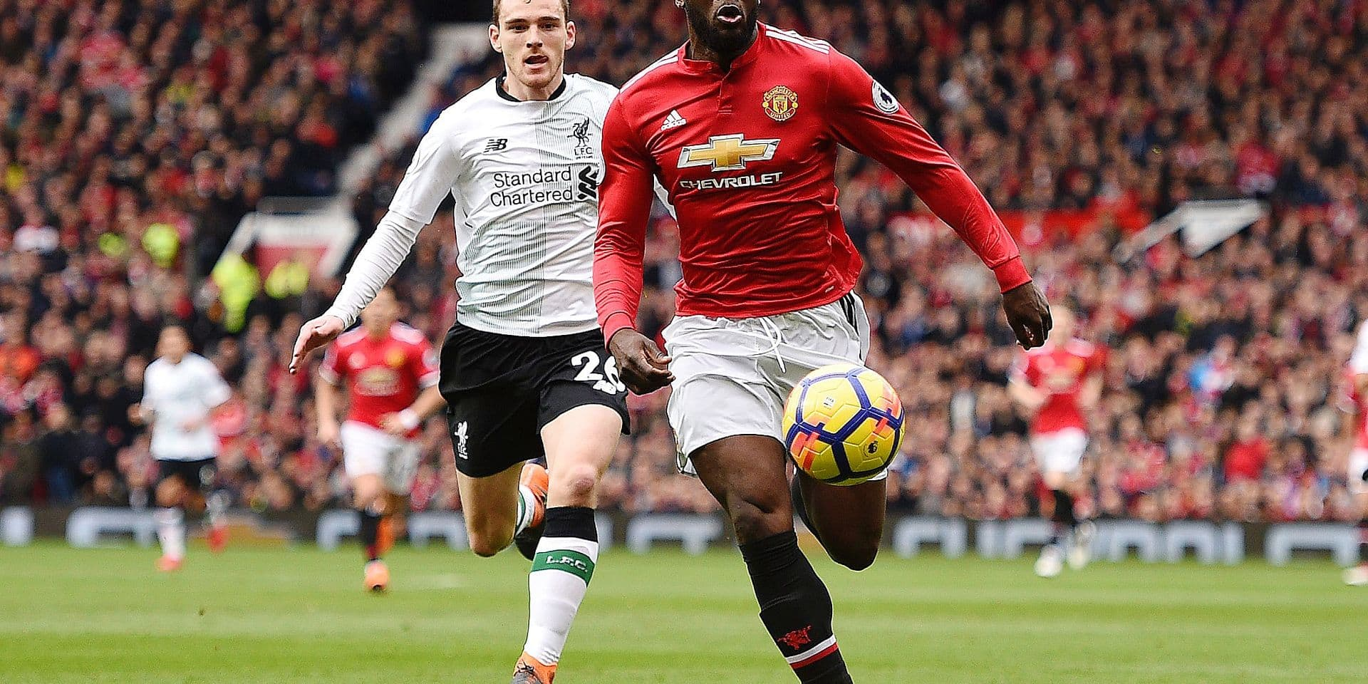 Manchester United's Belgian striker Romelu Lukaku (R) chases down the ball pursued by Liverpool's Scottish defender Andrew Robertson (L) during the English Premier League football match between Manchester United and Liverpool at Old Trafford in Manchester, north west England, on March 10, 2018. / AFP PHOTO / Oli SCARFF / RESTRICTED TO EDITORIAL USE. No use with unauthorized audio, video, data, fixture lists, club/league logos or 'live' services. Online in-match use limited to 75 images, no video emulation. No use in betting, games or single club/league/player publications. /