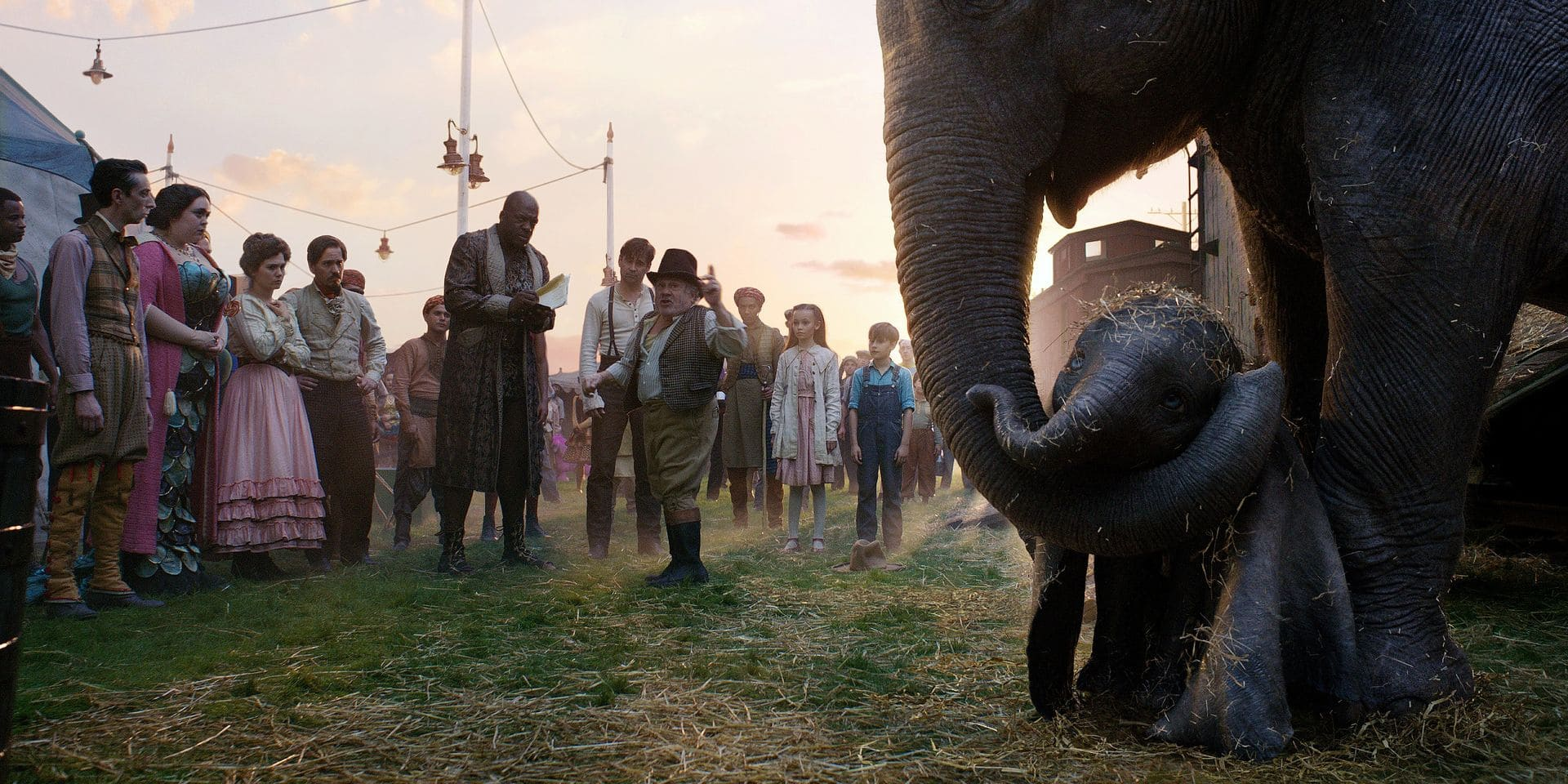 """CIRCUS FAMILY - In Disney's all-new live-action adventure """"Dumbo,"""" circus owner Max Medici (Danny DeVito) and circus performer Rongo the Strongo (Deobia Oparai)-plus the rest of their big-top team-welcome a newborn elephant with oversized ears to their tight-knit family. Directed by Tim Burton, """"Dumbo"""" flies into theaters on March 29, 2019. ©2018 Disney Enterprises, Inc. All Rights Reserved."""