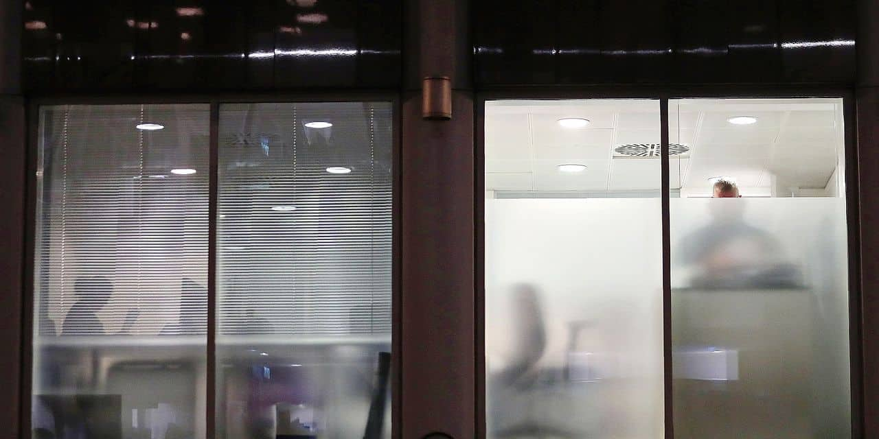 TOPSHOT - Peopel are seen through blinds searching inside the offices of Cambridge Analytica in central London on the evening of March 23, 2018, just hours after a judge approved a search warrant of the offices. British regulators on Friday, March 23, 2018, began searching the London offices of Cambridge Analytica, the scandal-hit communications firm at the heart of the Facebook data scandal, shortly after a judge approved a search warrant. / AFP PHOTO / Daniel LEAL-OLIVAS