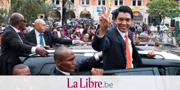 Madagascar's newly elected president Andry Rajoelina waves form his car as supporters cheer, in Analakely, in Madagascar, on January 8, 2019. - Madagascar's Constitutional Court on January 8, 2019 confirmed Andry Rajoelina as the winner of the Madagascar's presidential election after his opponent lodged a complaint alleging fraud. (Photo by Mamyrael / AFP)