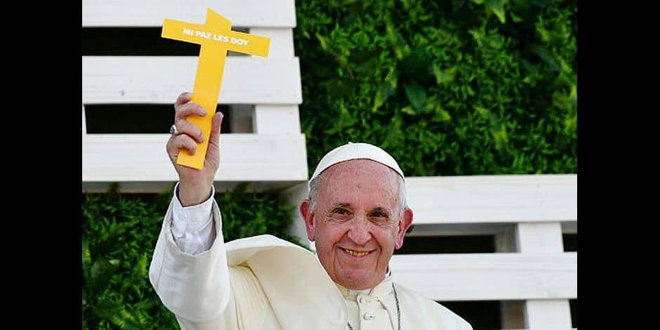 """Le Pape François salue la foule, tenant une croix arborant l'inscription """"je vous offre ma paix"""", près d'un temple à Santiago du Chili, le 17 janvier 2018"""