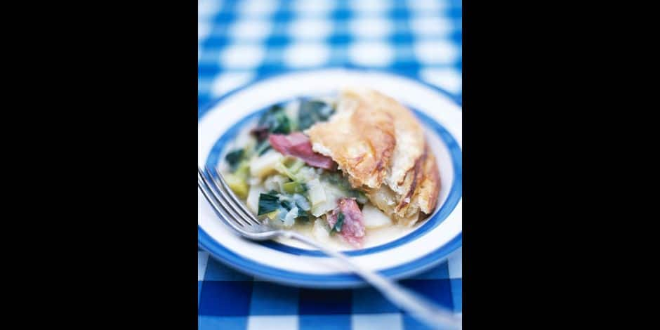 """""""Leek, potato and bacon pie with rough puff pastry top on blue and white plate"""""""