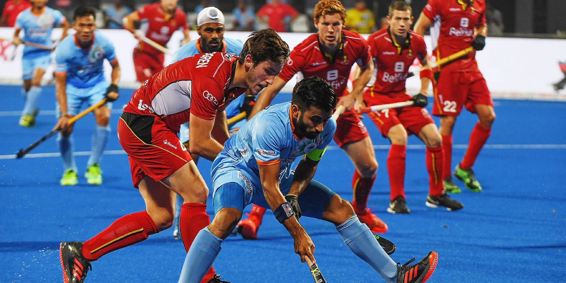 India's Manpreet Singh (C) tries to dribble past Belgium players during the field hockey group stage match between India and Belgium at the 2018 Hockey World in Bhubaneswar on December 2, 2018. (Photo by Dibyangshu SARKAR / AFP)