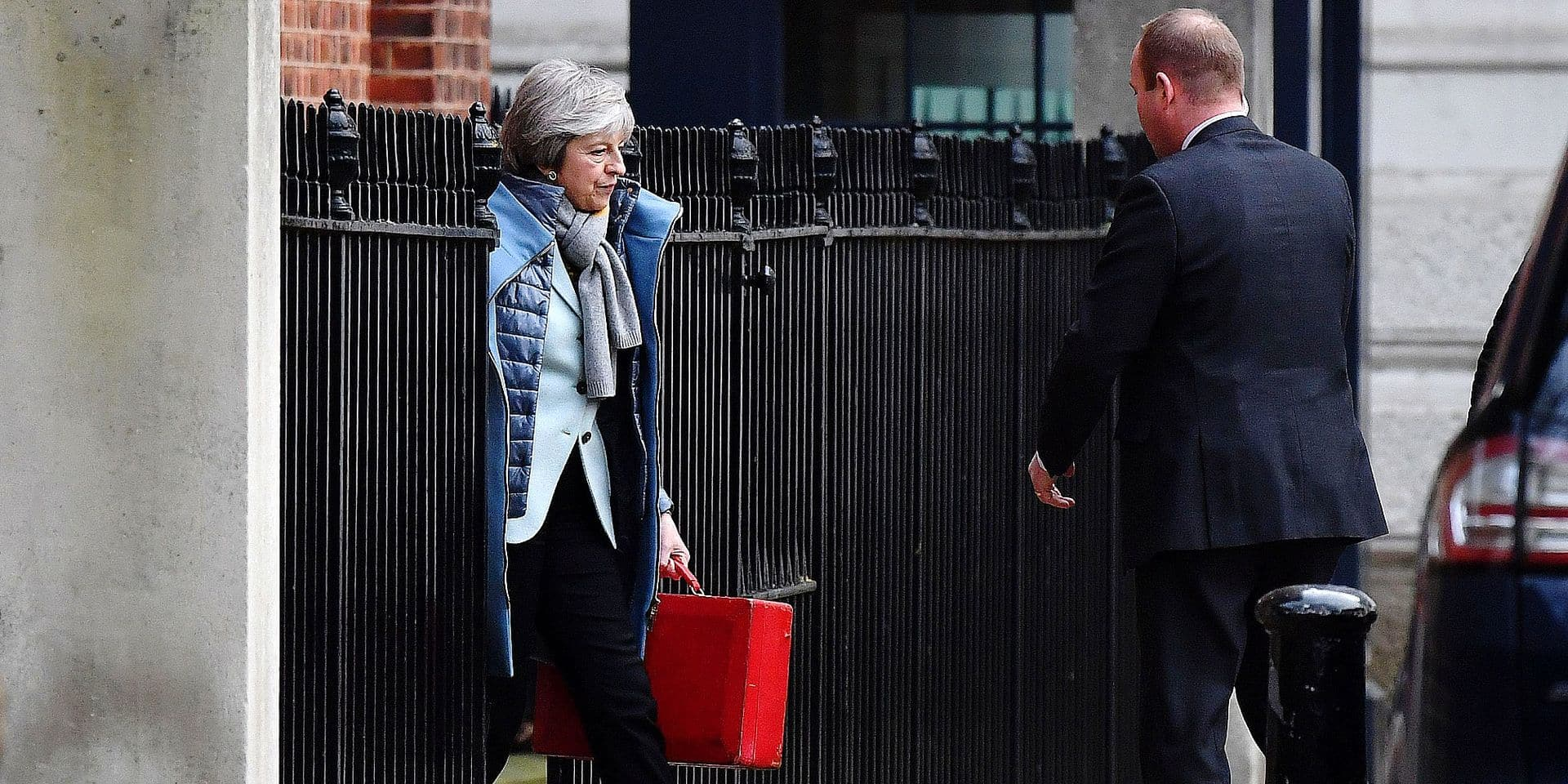 """Britain's Prime Minister Theresa May (L) leaves from the rear of 10 Downing Street in central London on January 18, 2019. - British Prime Minister Theresa May scrambled to put together a new Brexit strategy after MPs rejected her EU divorce deal, and insisted she could not rule out a potentially damaging """"no-deal"""" split. (Photo by Ben STANSALL / AFP)"""