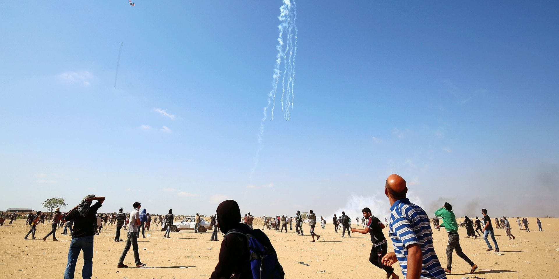 TOPSHOT - Palestinian protesters look up at falling tear gas cannisters dropped by an Israeli quadcopter drone during clashes near the border with Israel east of Khan Yunis in the southern Gaza Strip on May 15, 2018, amidst demonstrations marking 70th anniversary of Nakba -- also known as Day of the Catastrophe in 1948 -- and against the US' relocation of its embassy from Tel Aviv to Jerusalem. / AFP PHOTO / SAID KHATIB