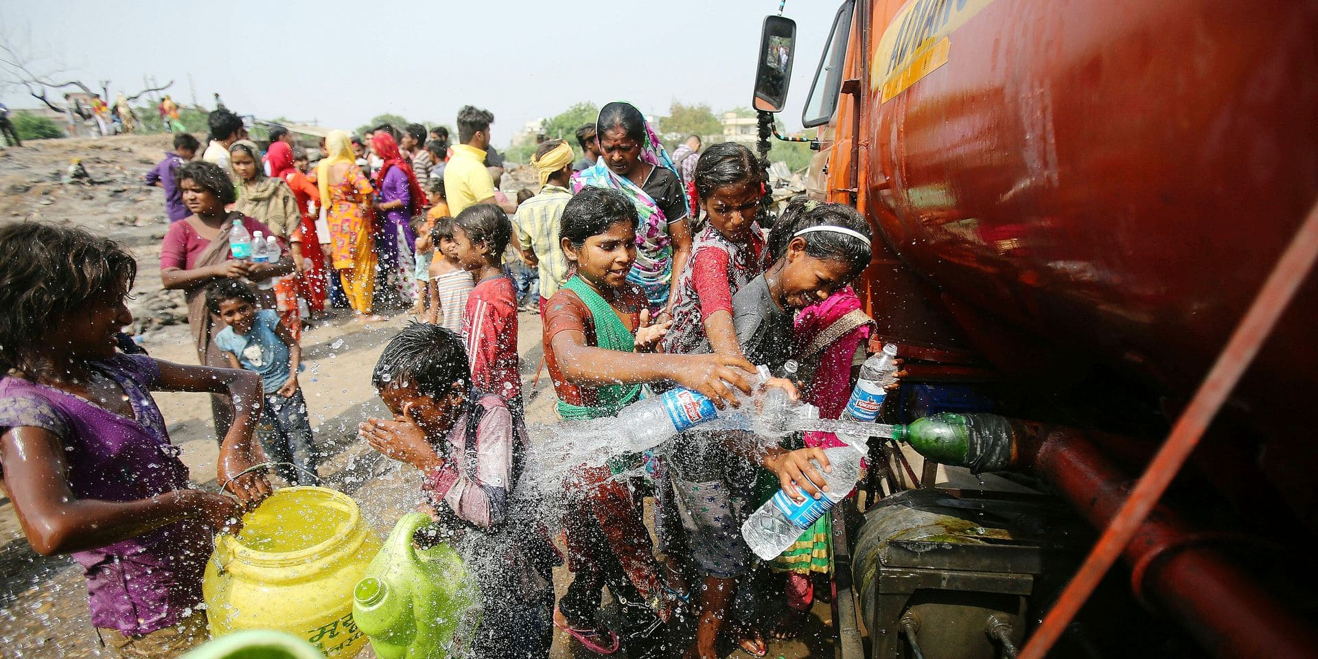 People fill containers with water from a mobile tanker at a slum area on the outskirts of Jammu, India, Monday, June 3, 2019. Many parts of India are experiencing heat wave conditions with temperature hovering above 45 degree celsius (113 fahrenheit). (AP Photo/Channi Anand)