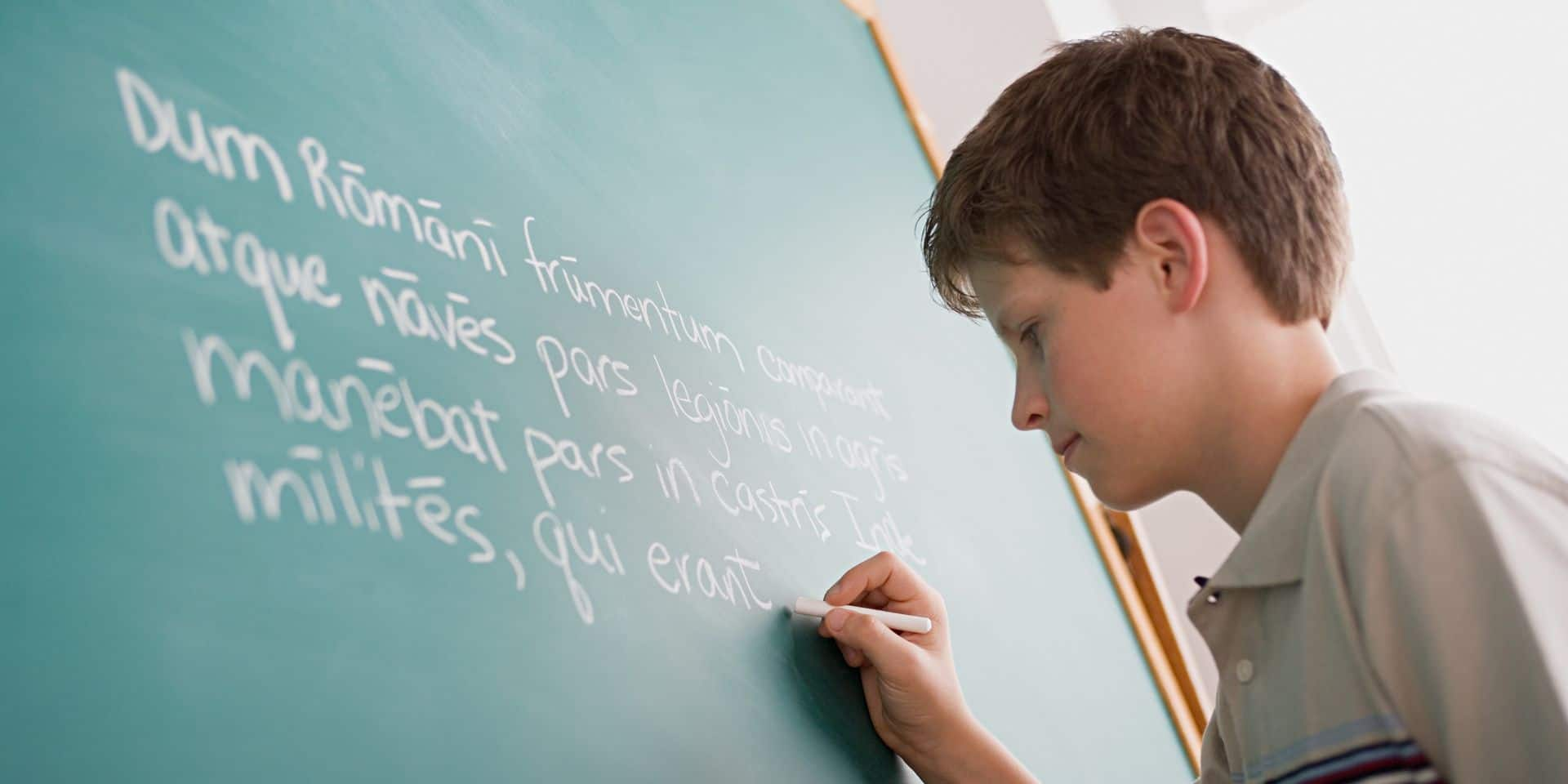 Student writing latin on the board