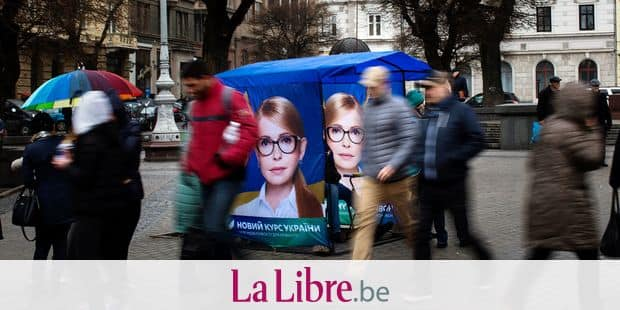 People walk past a stand of electoral information with the a portrait of Yulia Tymoshenko, candidate for 2019 presidential elections, in Lviv, Ukraine, Thursday, March 28, 2019. Presidential elections will be held in Ukraine on 31 March 2019. (AP Photo/Emilio Morenatti)