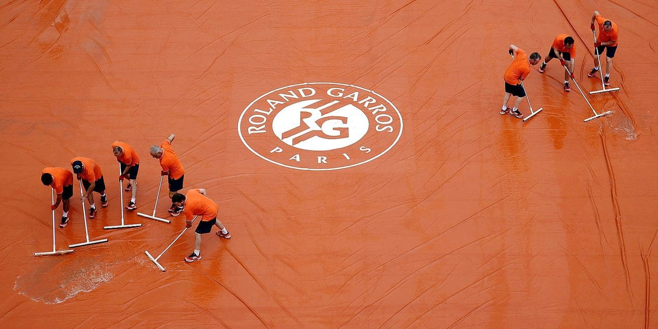 Stadium employees remove water from the court as play is being delayed by rain during the French Open men's quarterfinals at the Roland Garros stadium, Wednesday, June 6, 2018 in Paris. (AP Photo/Alessandra Tarantino)