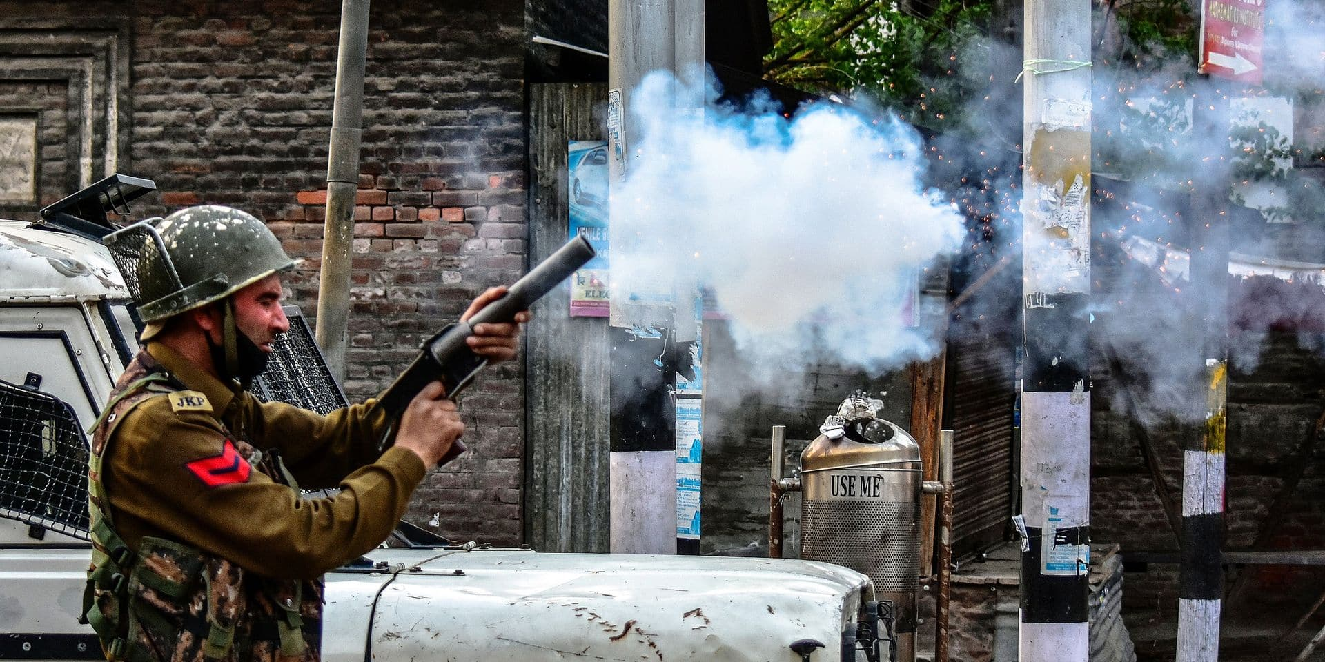 April 2, 2018 - Srinagar, India - An Indian policeman fires a tear gas shell towards Kashmiri protesters during a protest against the killings in separate encounters in south Kashmir. Muslim majority areas of Kashmir Monday observed a complete shutdown to protest the killing of 4 civilians and 13 rebels in separate encounters in south Kashmir. Authorities imposed curfew in several areas to stop street protests. The call for shutdown was given by the separatist groups. Stone-pelting incidents were reported from some parts of the Kashmir valley. Meanwhile, authorities also suspended mobile internet services in Kashmir valley. PICTURE NOT INCLUDED IN THE CONTRACT ! Only BELGIUM !